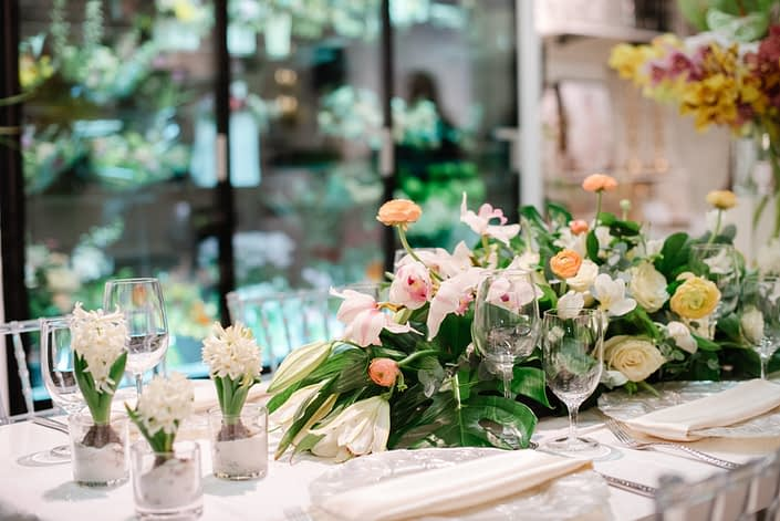 Hyacinth flowers in clear glass vases with floral arrangement in peach ranunculus and white flowers with monstera leaves and clear glass chiavari chairs