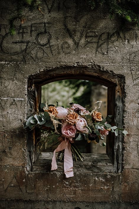 bridal bouquet sitting in concrete wall window designed with pink ohara garden roses, toffee roses and gold plumosa and cinerea eucalyptus with blush silk ribbon tie
