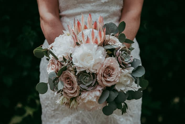 bride in white lace wedding dress holding a bouquet with silver dollar eucalyptus, pale pink king protea, blush quicksand roses, sage lola succulents, blushing bride protea and pale blush peony
