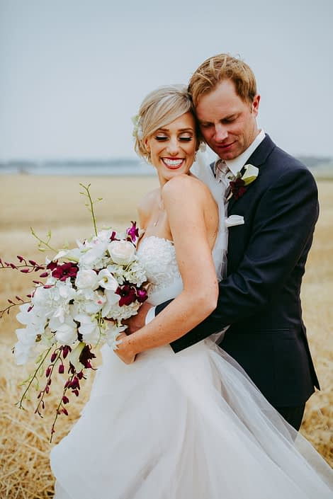 bride and groom in alberta summer wheat field holding a modern cascade bridal bouquet designed with white dendrobium orchids, burgundy dendrobium orchids and white roses