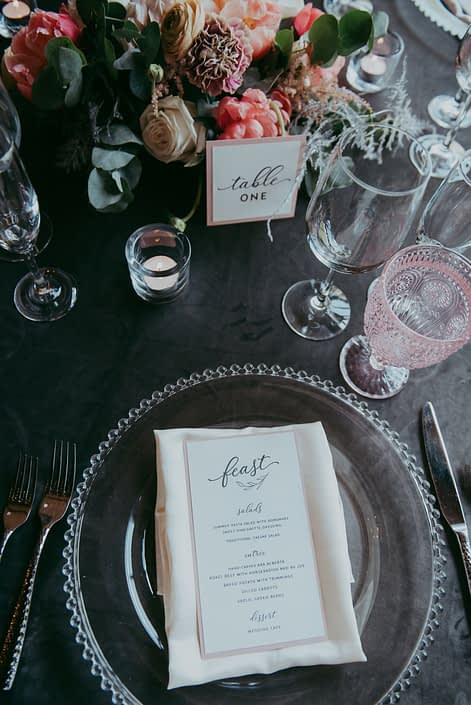 Table setting for Canyon Ski Resort Open House 2019 featuring blush goblet, silver lucca flatware, a smoked grey table cloth, stationary and coral and blush floral arrangement with silver metallic plumosa and eucalyptus greenery.