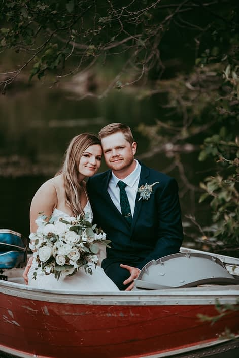 Bride and groom with white bridal bouquet designed with astilbe, ranunculus, tibet roses, sweet peas, scabiosa pods and eucalyptus