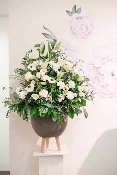 Fresh flower arrangement in grey concrete planter designed with white flowers and greenery