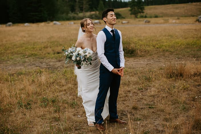 Bride and groom first look with white and blue bridal bouquet featuring delphinium, eryngium, forget me not, garden rose, ranunculus and sweet pea with eucalyptus