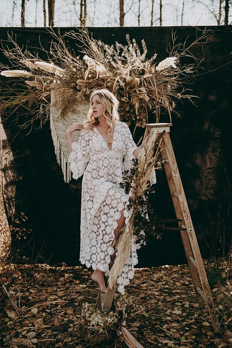 blonde boho bride on ladder with dried pampas grass and dried floral backdrop in the fall in the woods
