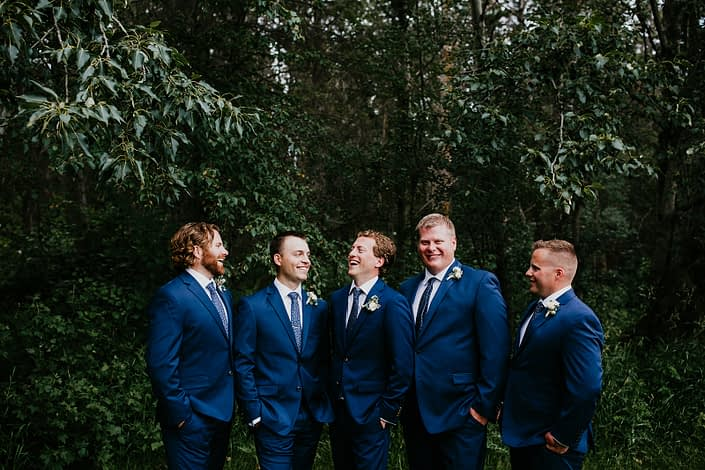 Groom and groomsmen wearing navy suits and classic white boutonnieres.