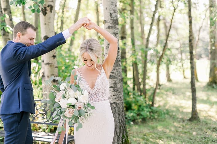 Kayla and Joel dancing while Kayla holds a bridal bouquet designed with white o'hara garden roses, white ranunculus, quicksand roses, white astilbe, olive branches and fresh eucalyptus.