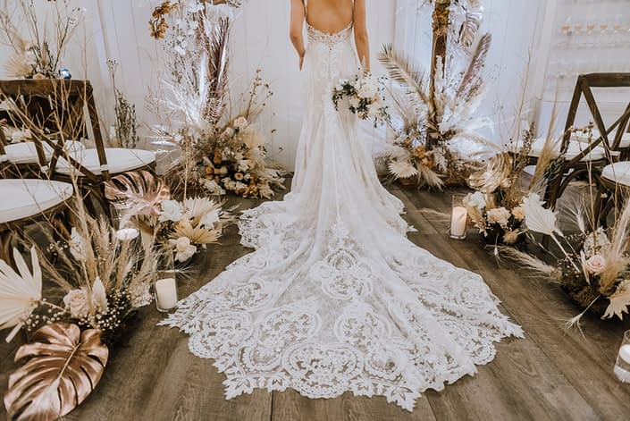 Lace bridal gown train surrounded by arrangements made of gold painted monstera leaves, painted sago palm, pampas grass, playa blanca roses, quicksand roses and other flowers and dried foraged leaves and branches.