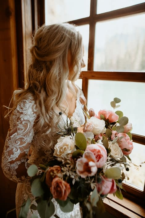 Bride looking out window with blush pink, white and blue bouquet designed with roses, tulips, peonies, eryngium and eucalyptus
