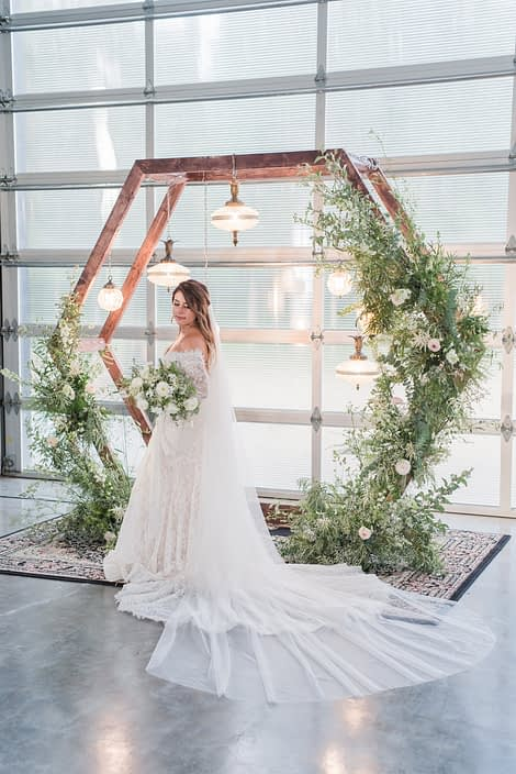 Bride holding white and green bridal bouquet beside a wooden hexagon archway covered with wild and natural green and white botanicals.