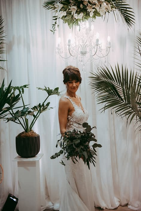 bride with greenery bridal bouquet and tropical plants underneath chandelier and floral arrangement