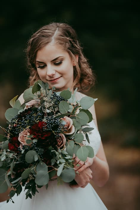 bride portrait with side braids and bouquet with burgundy dahlias and red roses and amnesia roses and navy viburnum berries and mixed eucalyptus greenery handtied with ribbon
