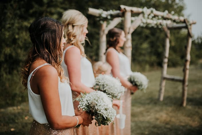 Bridesmaids in rose gold sequin skirts holding bridesmaid bouquets of babies breath and eucalyptus