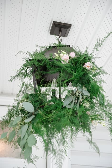 Black chandelier decorated with plumosa and silver dollar eucalyptus