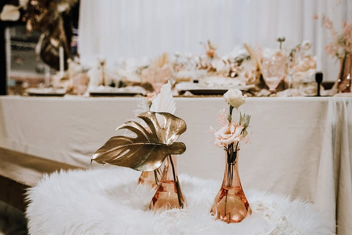 Pink bud vases filled with metallic gold dyed monstera leaf, and blush and ivory flowers.