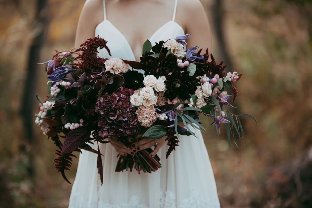 Bride in simple white dress holding a front facing bride bouquet designed with burgundy maranthus, hydrangea, blush spray roses, blush carnations and purple clematis for an autumn wedding