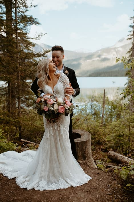 Bride and groom in the forest next to Emerald Lake and the Rocky Mountains with a blush pink and white bridal bouquet made of peonies, roses and tulips