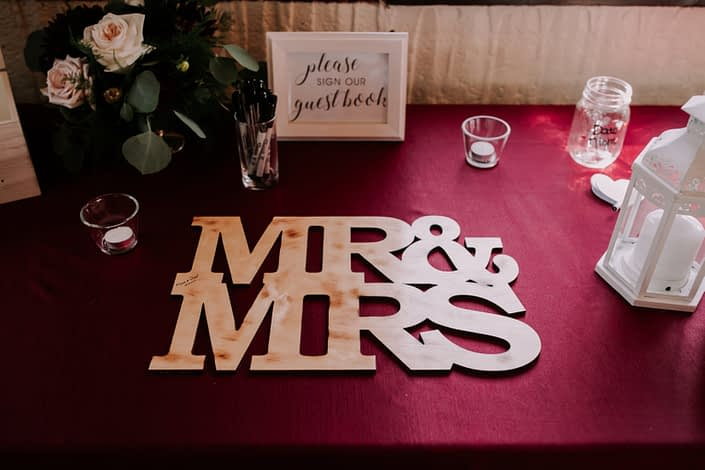 Guest book table with burgundy and blush flower arrangement.