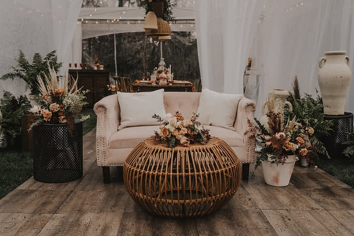 Modern boho seating area with rattan elements and terracotta toned floral arrangements with terracotta pottery and ceramics