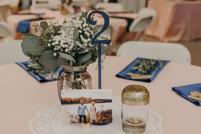 rustic table centerpiece with mason jar and blue ribbon and babies breath and eucalyptus and photograh of bride and groom and blue napkins