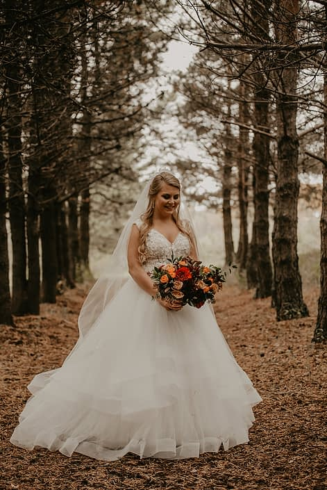 Bride, Haley, with her rustic fall bridal bouquet designed with hearts garden roses, burgundy dahlias, golden mustard yellow roses, orange spray roses, hypericum berries, italian ruscus and seeded eucalyptus.