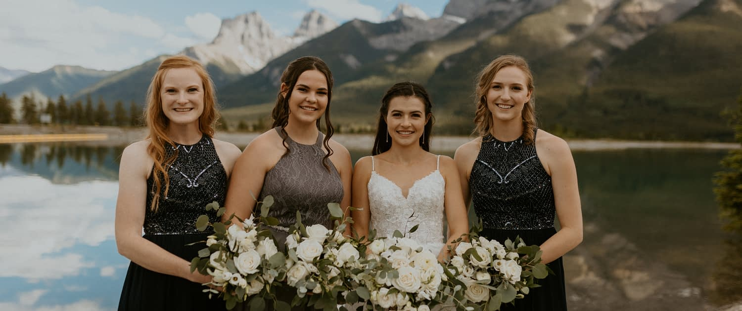 Bride and bridesmaids; white, navy and charcoal dresses; Rocky Mountains; white bouquets designed with ranunculus, roses, lisianthus, sweet peas