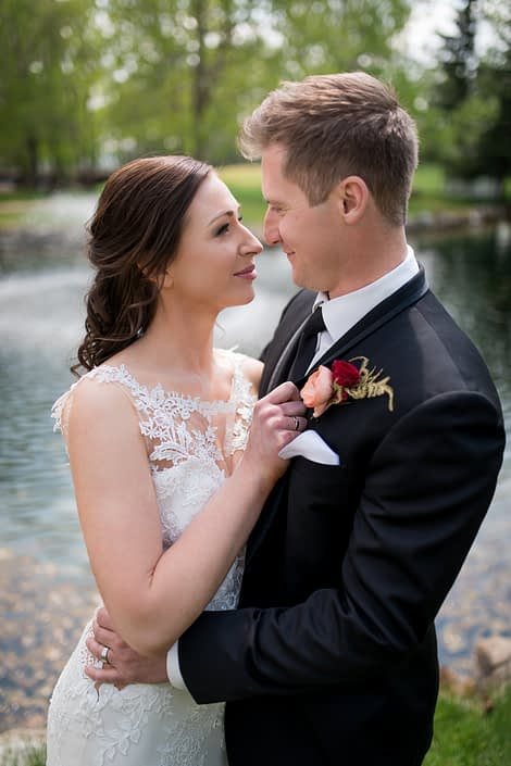 bride in white lace wedding dress with groom in black tuxedo wearing a boutonierre with peach ranunculus and burgundy rose and gold plumosa accent