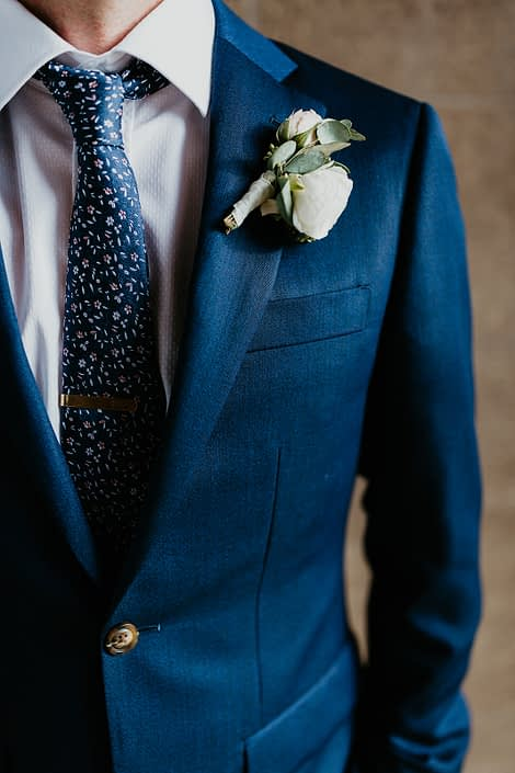 Groom wearing a navy suit and a classic white boutonniere made with spray roses and eucalyptus.