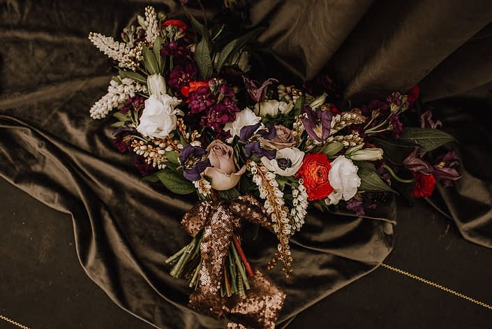 alternative bridal bouquet with red ranunculus and white anemone and white pieris and purple clematis and white lisianthus with a copper sequin handle wrap