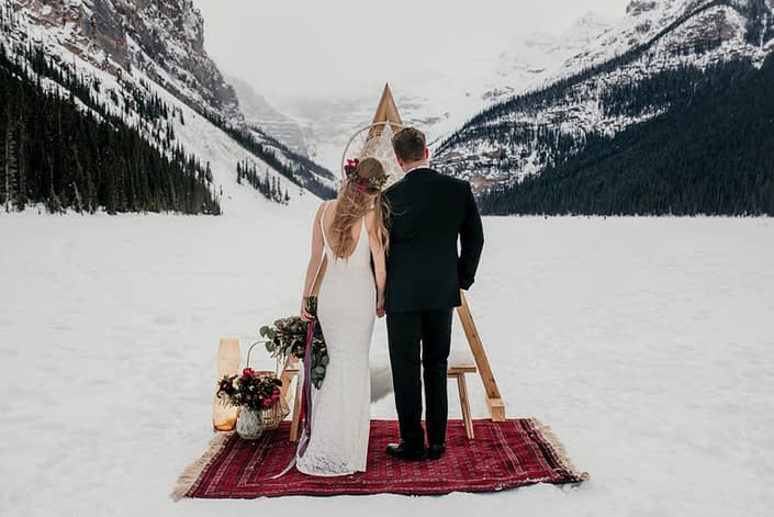 lake louise elopement with a triangle archway and burgundy floral accents
