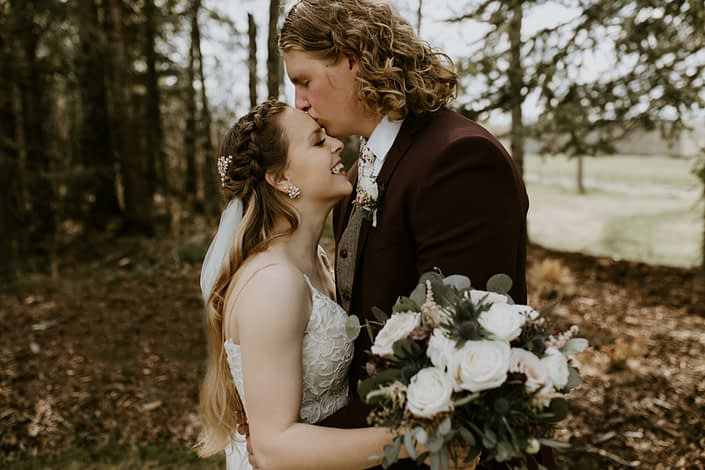 Groom kissing bride's forehead with a blush, white and burgundy bouquet