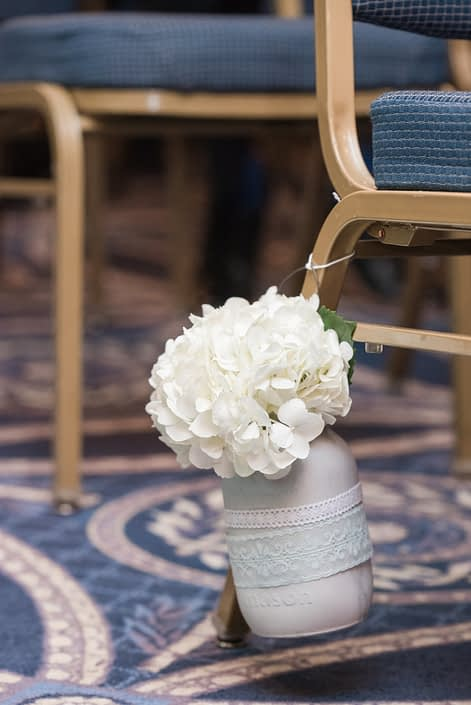 Aisle marker floral arrangement for Megan and Steven's Rustic Pastel Wedding. A white hydrangea in a painted mason jar with lace detail.