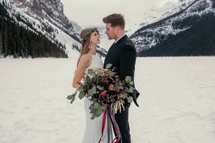 bride and groom in lake louise with organic greenery and burgundy bridal bouquet