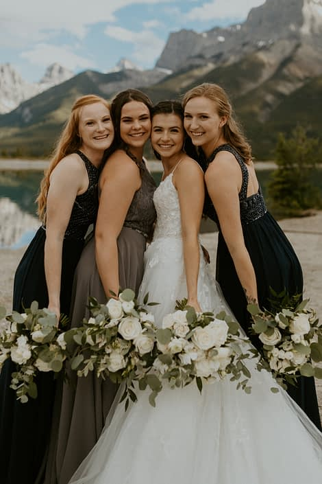 Bride and bridesmaids wearing white, grey and navy with white bouquets designed with roses, ranunculus, lisianthus and sweet peas