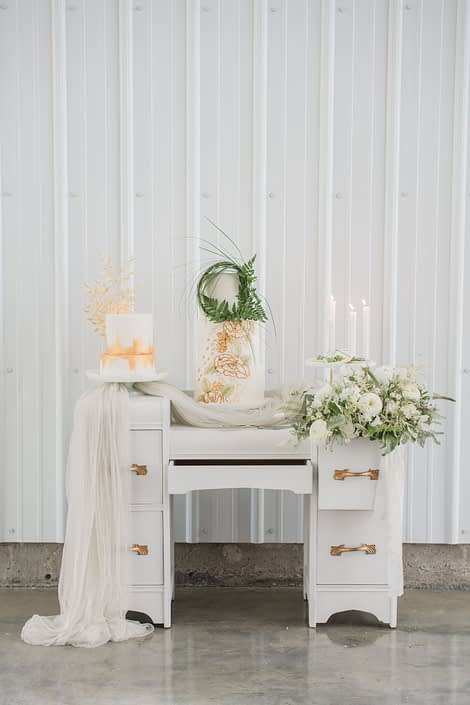 White vintage vanity covered with flowers and cakes.