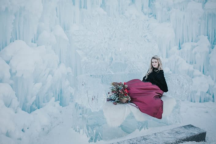 Bride sitting on ice couch at the edmonton ice castles with burgundy bouquet
