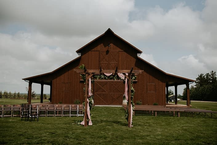 Sweet haven barn ceremony set up including wooden pews and a wooden archway covered in a fresh greenery garland with burgundy and dusty rose flowers.