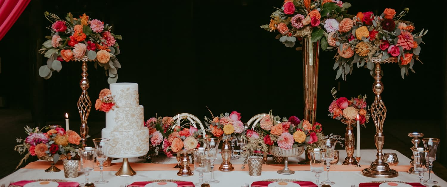 Bold fuchsia and orange tablescape designed with high and low floral arrangements, gold accented place settings and a white wedding cake.