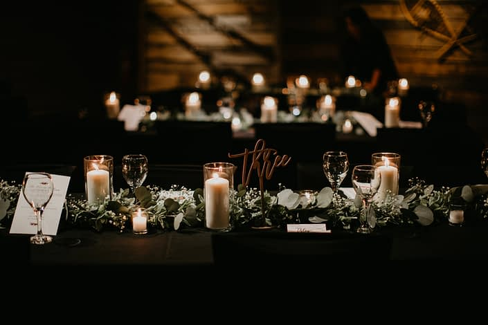 Reception decorated with long tables with black table cloths, eucalyptus runner with babies breath, candles and rose gold table number signs