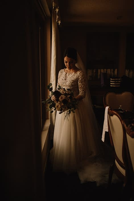 bride in long sleeved lace top wedding dress with bouquet of burgundy dahlia, blush quicksand roses and ivor garden roses and eucalyptus