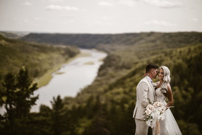 Bride and groom overlooking a rivervalley with glam boho bridal bouquet featuring roses, pampas grass and orchids.