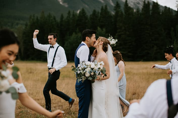 Bride and groom kissing in Rocky Mountains with white and blue bridal bouquet