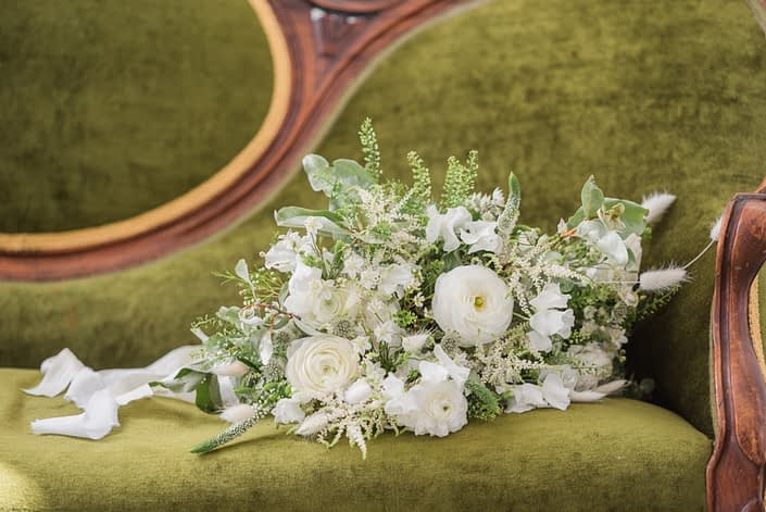 White and green romantic bridal bouquet designed with white flowers such as poopies, ranunculus, astilbe, veronica, wax flower, bunny tail and sweet peas with a mixed variety of greenery.