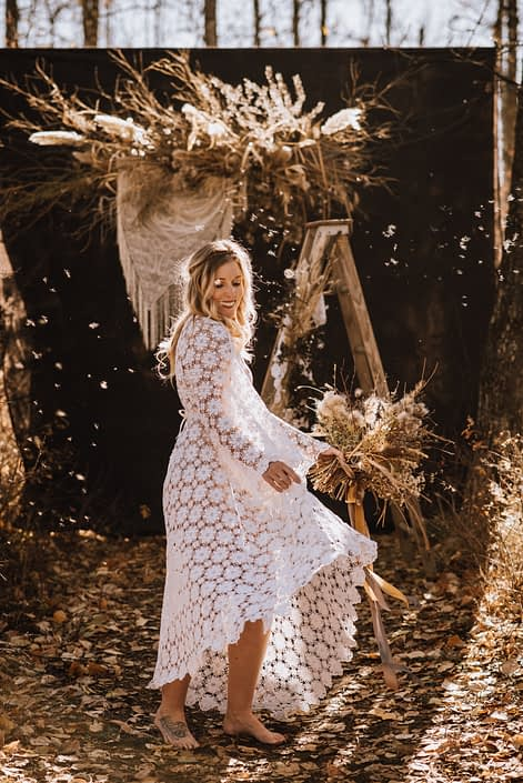 playful sunlit barefoot boho bride with crochet dress in fall with bouquet of dried florals with pampas grass and dried floral backdrop with crochet hanging