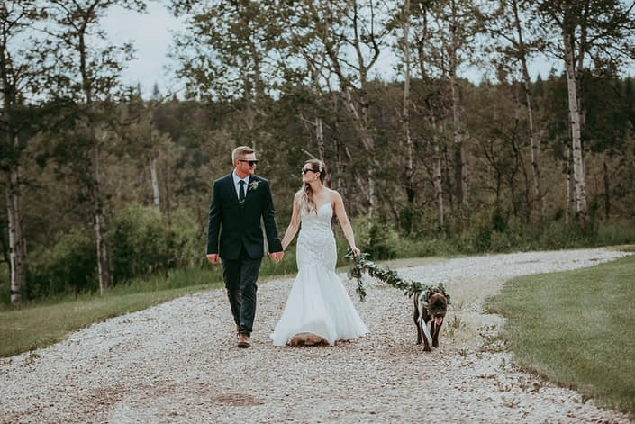 Bride and groom walking dog with eucalyptus garland collar and leash
