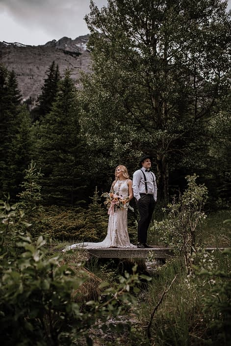 Bride and groom in a mountian wedding photo with organic bridal bouquet in copper and blush with groom in black hat and suspenders