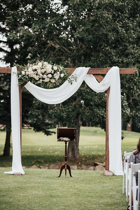 Wedding archway with white draping and flowers