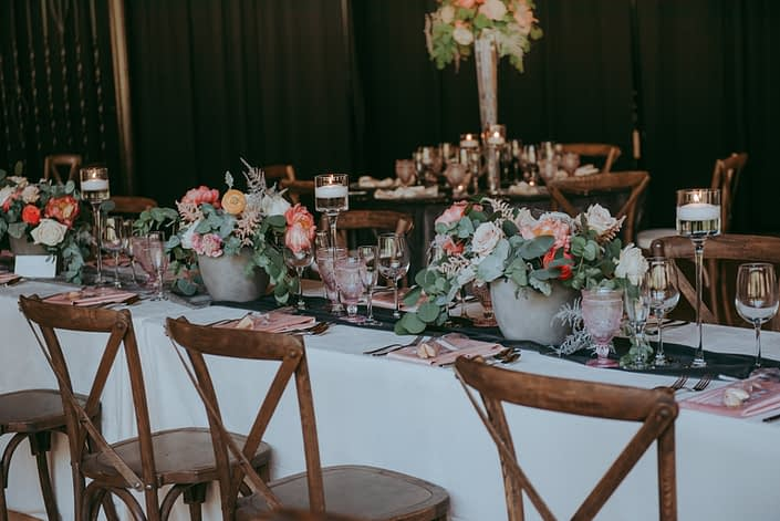 Rectangular table decorated with an ivory velvet table cloth, smoked grey table runner, blush goblets, and coral and blush floral arrangement in concrete vases featuring coral charm peonies, quicksand roses, playa blanca roses, peach ranunculus, silver plumosa and eucalyptus; vineyard chairs.
