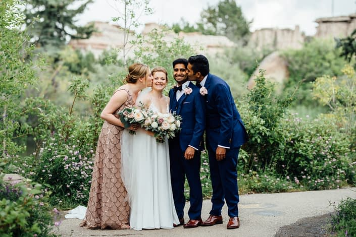 Bridesmaid kissing bride's cheek, groomsman kissing groom's cheek; men wearing navy suits and blush boutonnieres; bride and bridesmaid holding blush and white bouquets featuring roses, ranunculus and eucalyptus.