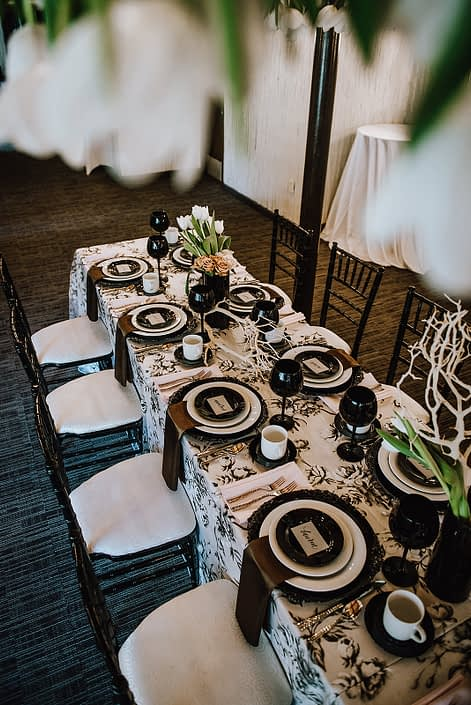 Rectangular table set with an ivory and black marie noir linen tablecloth, black and white plates, black goblets, and black chiavari chairs; black vases were filled with white dream tulips, toffee and quicksand roses and Mazanita branches.